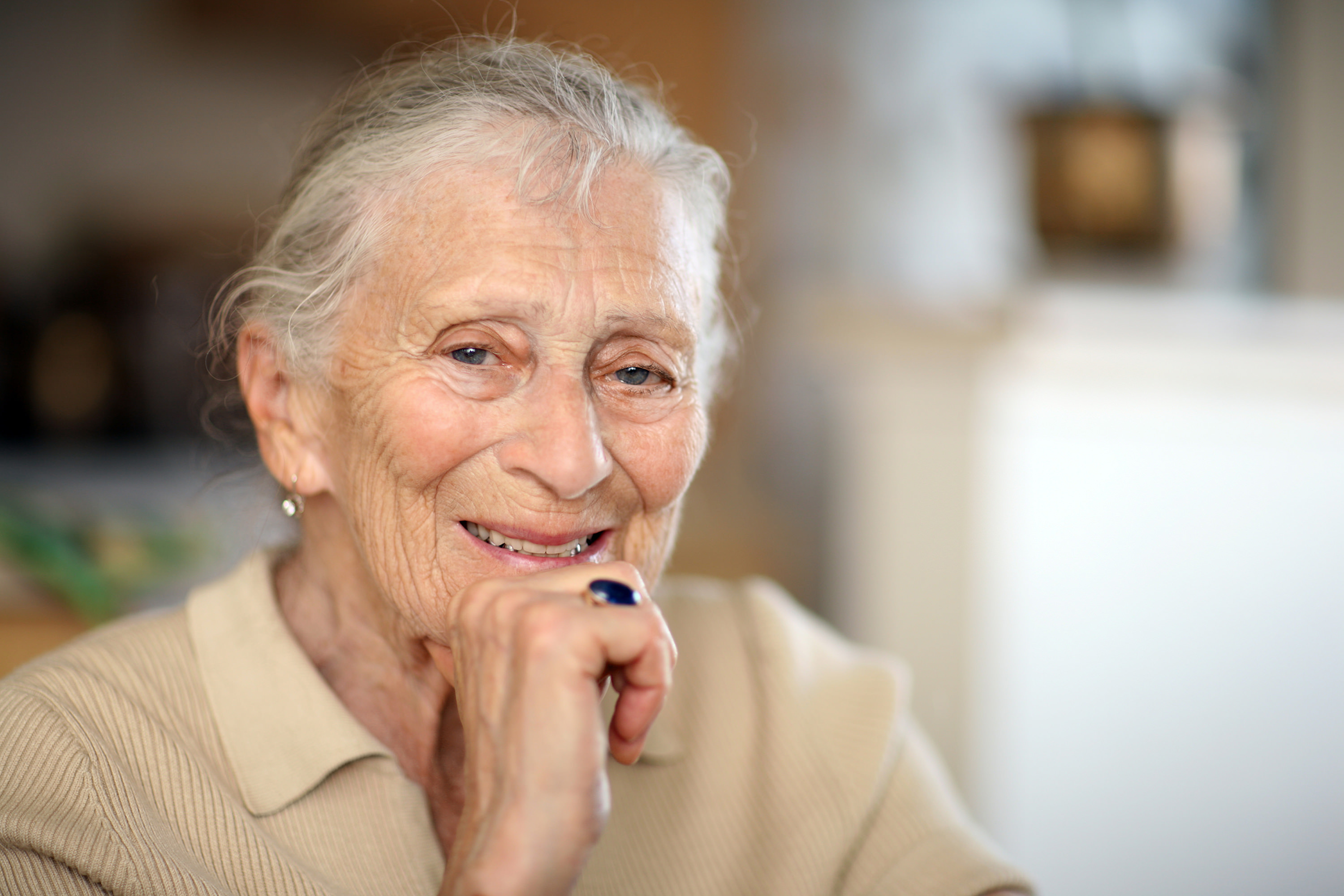 older woman with hand on chin, smiling