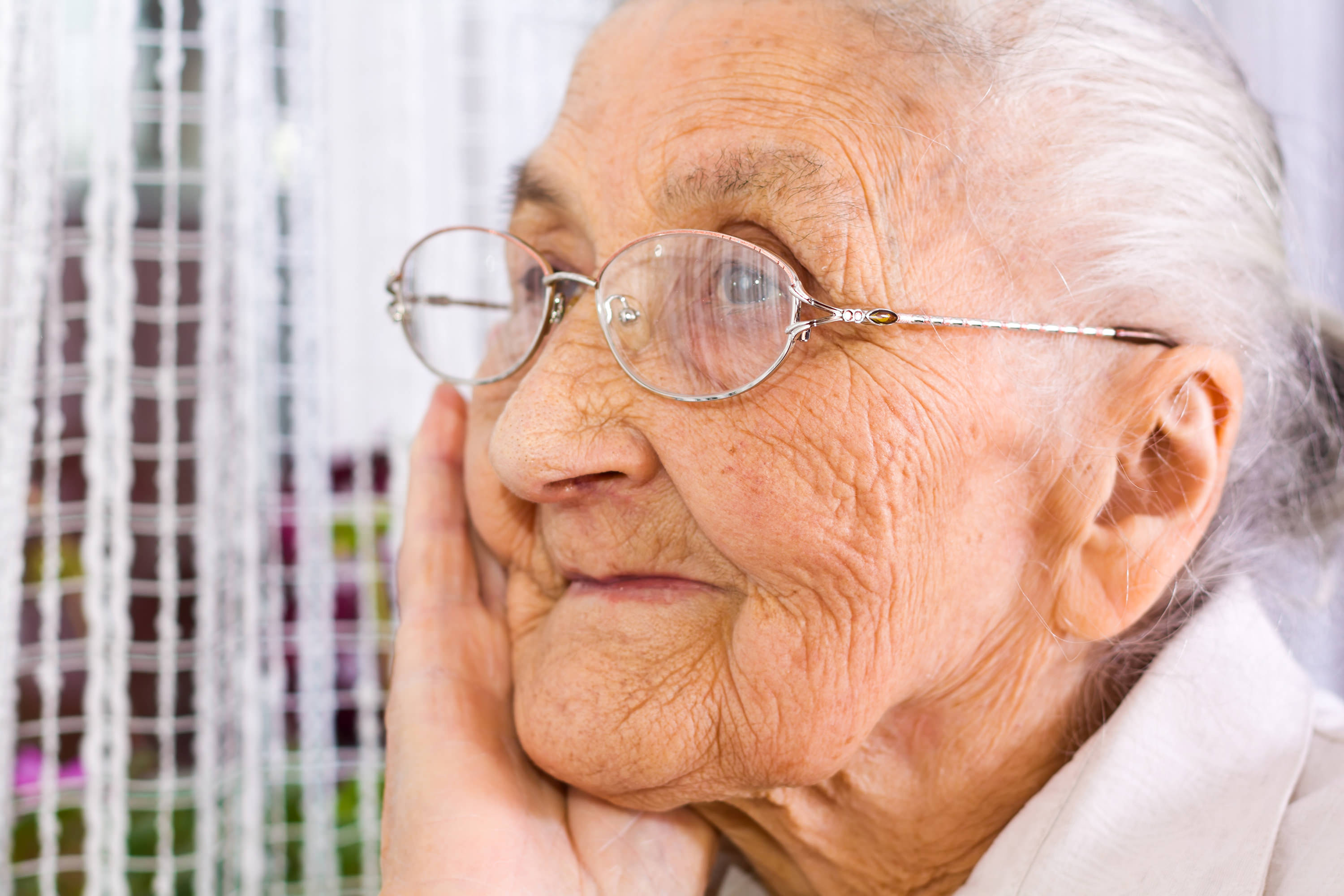 older woman with glasses thinking