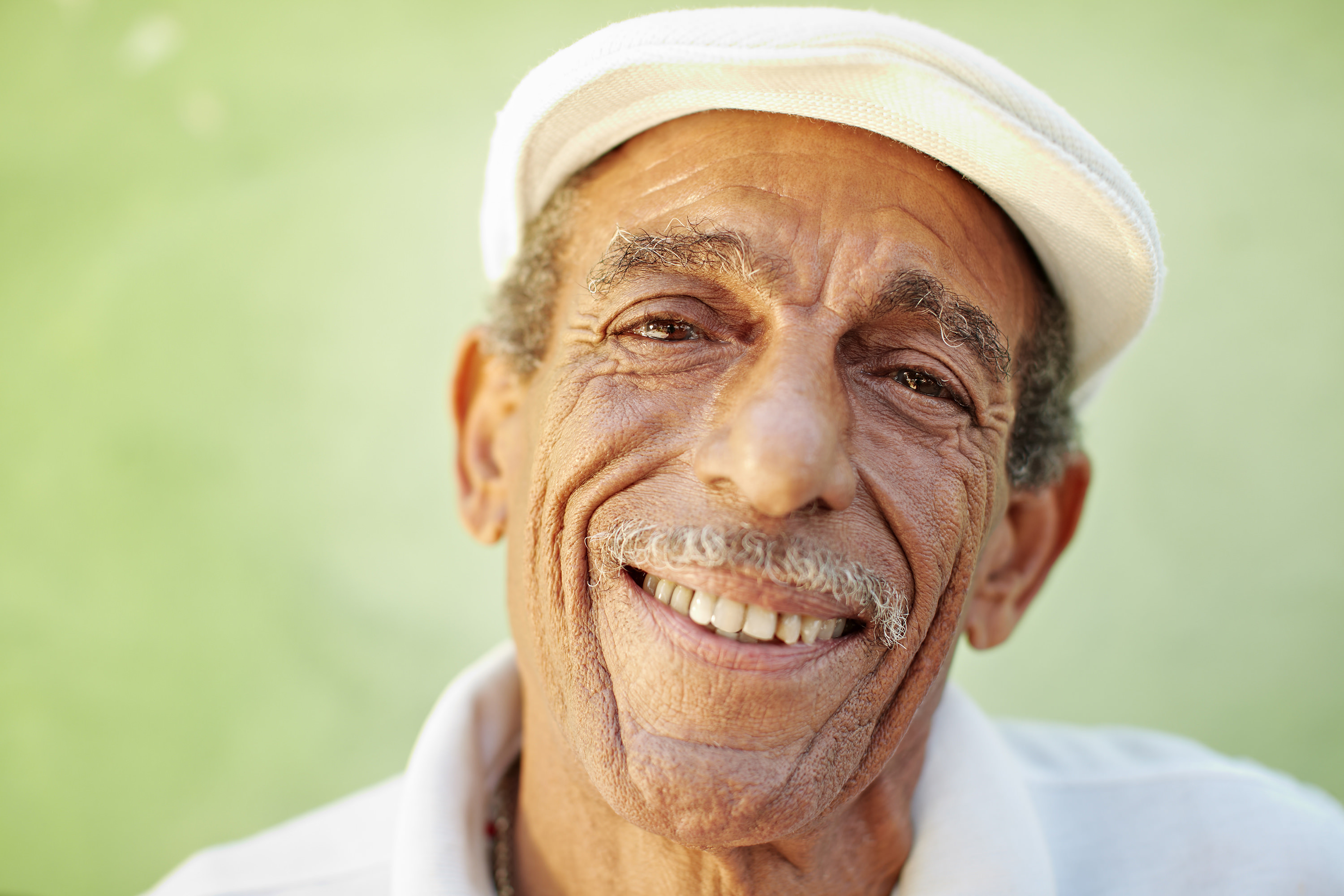 older man with bunnet smiling