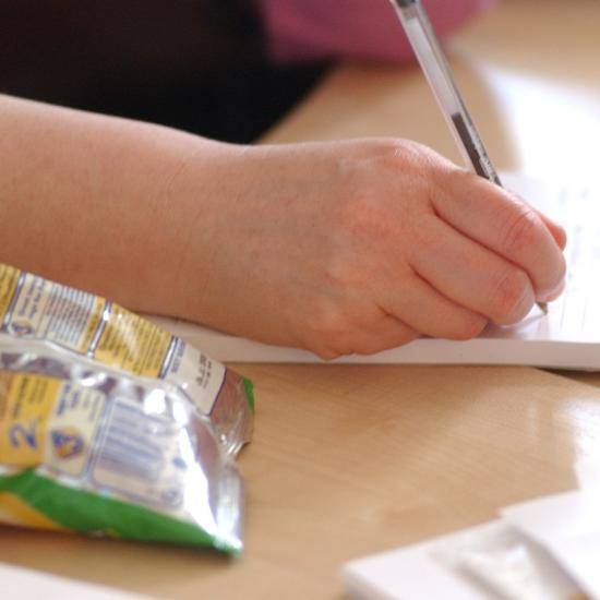 Picture of a hand writing a note