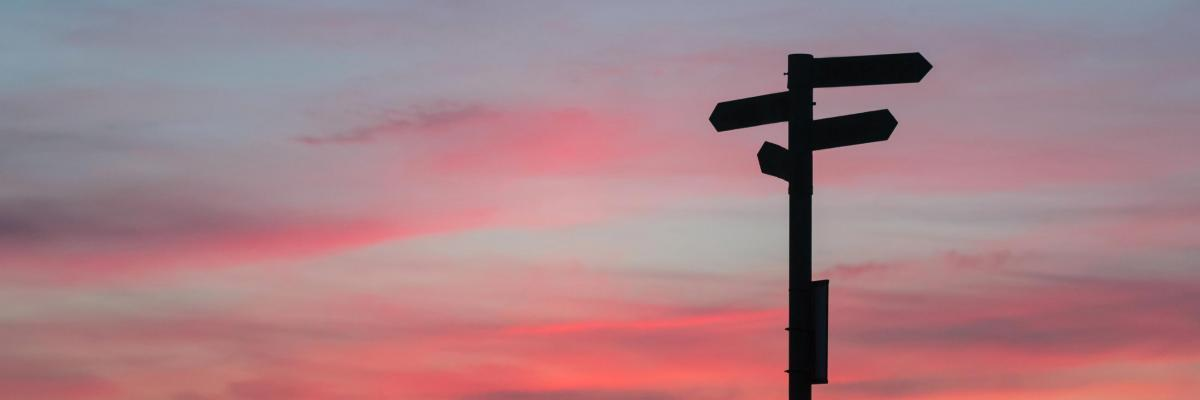 Signpost silhouetted against sunset sky
