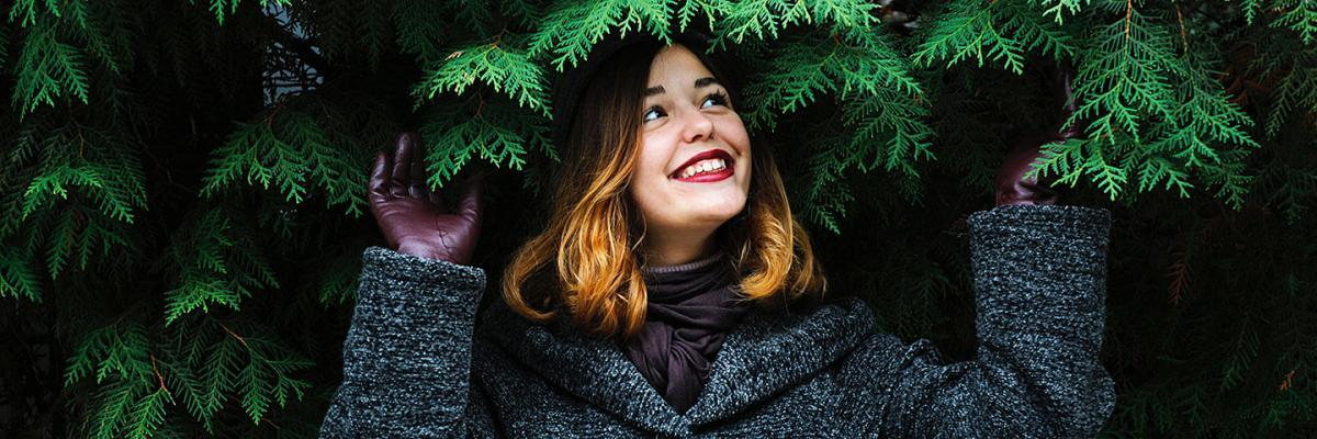 Smiling woman sheltering under trees